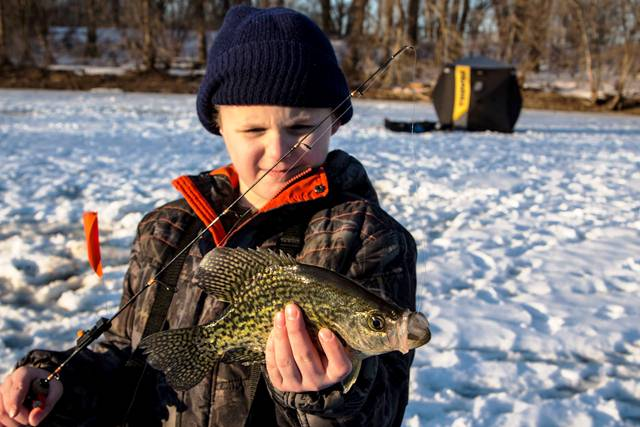 boy catching crappie through the ice